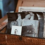 Brown box with lid open stuffed with black and white photographs of relatives and a baby. Do you know yourself?