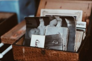 Brown box with lid open stuffed with black and white photographs of relatives and a baby. Self-awareness begins with knowing your lifelong patterns
