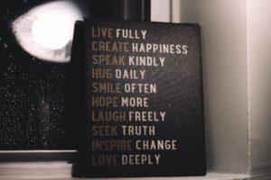 Sign stating a list: live full, create happiness, speak kindly, hug daily, smile often, hope more, laugh freely, seek truth, inspire change, love deeply. Missing from the list is grow your self-awareness.