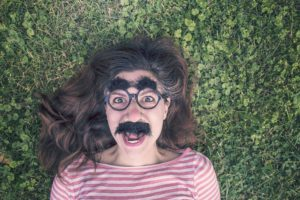 Woman lying on grass with Groucho Marx eyebrows, mustache, and glasses as representing impostor syndrome