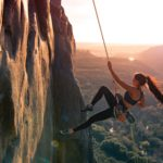 Strong Woman hanging off side of rock face swinging with sunset in background. Confidence versus fear.